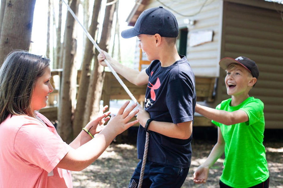 A young camper is balancing on a cable one foot above the ground and is holding a rope. Two participants on either side support the camper by standing in a position known as spotting. Everyone is smiling.