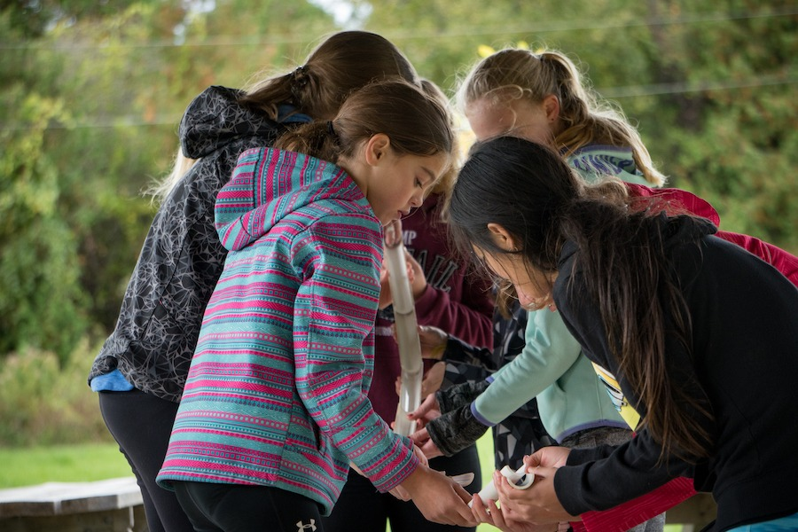 Four campers in close proximity to one another try to successfully align plastic tubes for an activity known as marble tubes at summer camp.