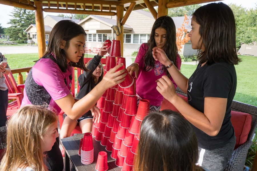 A group of five campers are standing in a gazebo attempting to stack a tower of red solo cups.