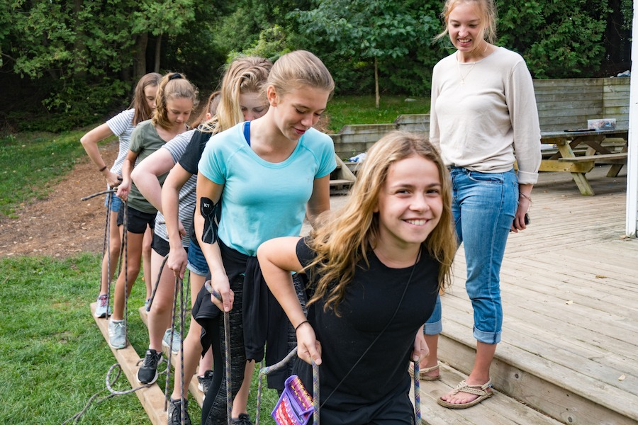 Six campers on a field are holding onto strings attached to wooden planks under their left and right feet trying to walk together and successfully move the planks forward. They are supervised by a staff member named Piglet.