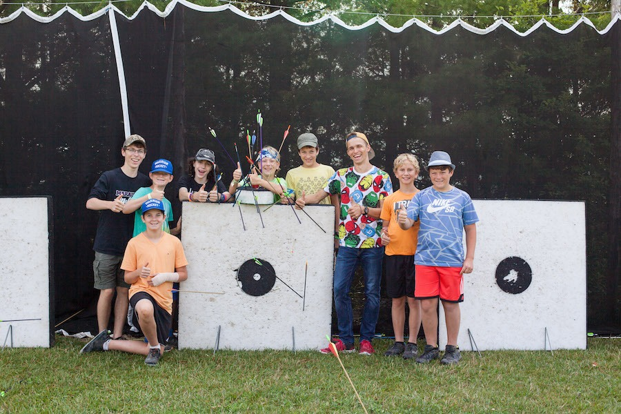 A group of seven campers with two staff stand behind archery targets smiling for a group photo.