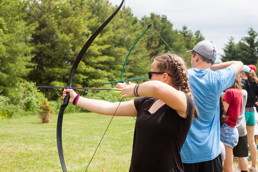 A camper aims their bow and arrow at a target, drawing the bow string back ready to fire.