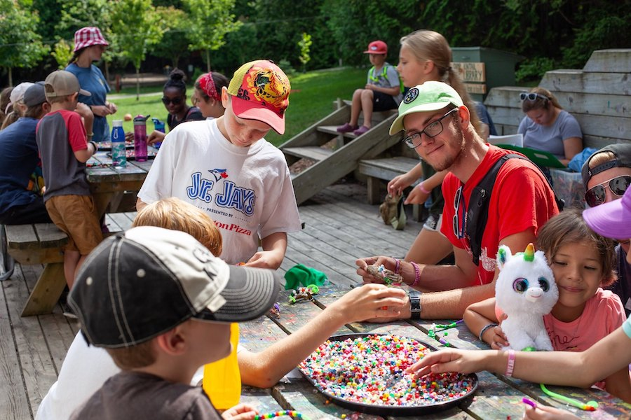 A group of campers and staff sit at picnic tables on an arts and crafts porch putting beads on pipe cleaners to create beaded snakes.