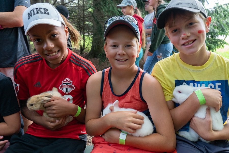 Three campers sit on a bench smiling and holding baby bunnies at summer camp.
