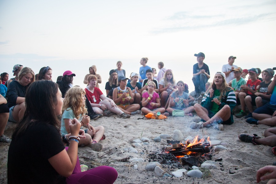 A group of campers and staff seated on wooden log benches around a campfire on the beach. Lake Huron is behind them.