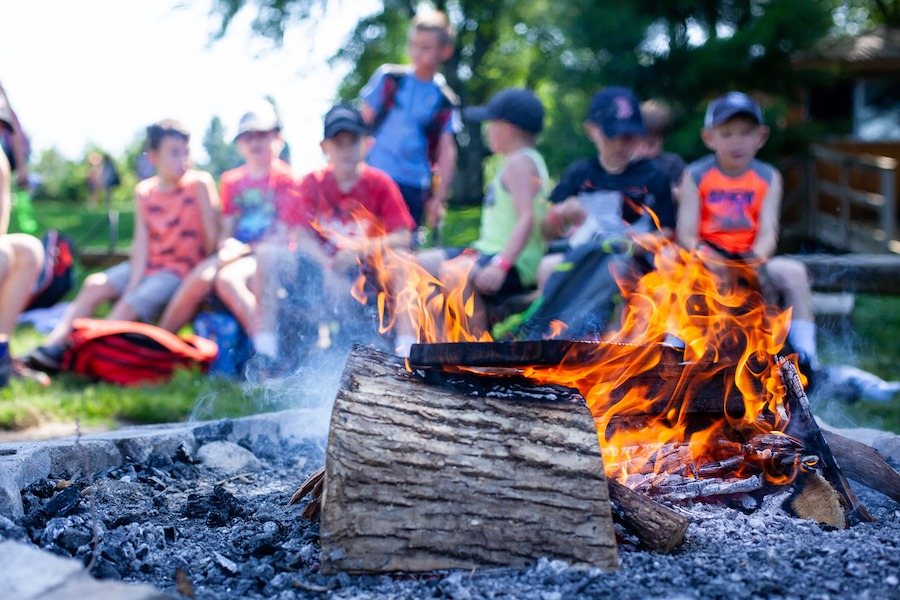 Close up campfire with campers and staff seated on wooden log benches in the background and summer camp.
