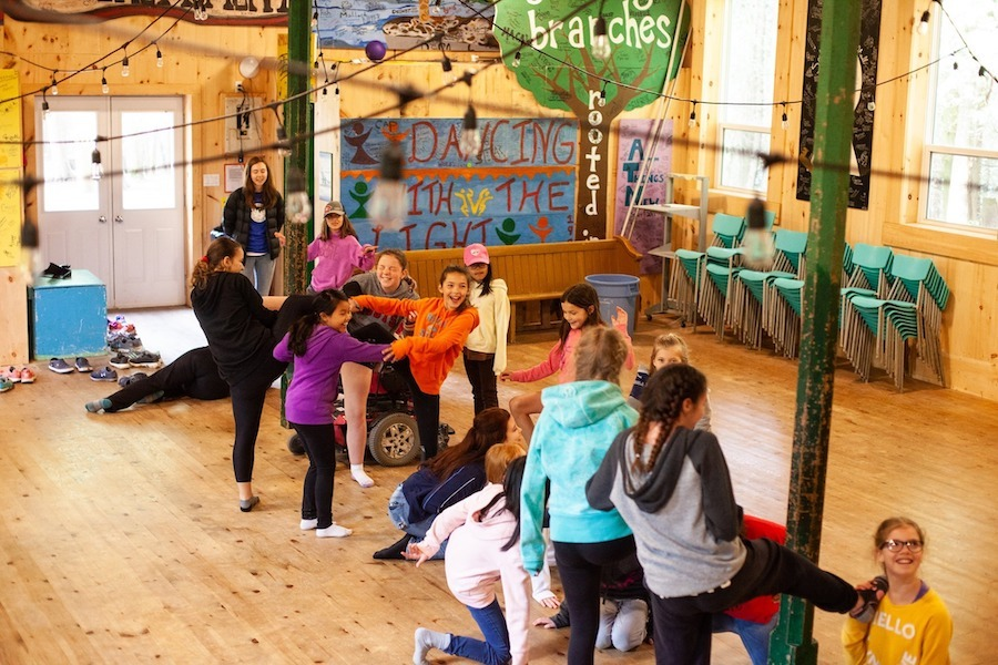 A group of campers in two separate lines meet together in the center of the indoor Rec Hall at Camp Kintail, posed with a foot on the other's shoulder for an activity known as Simon Says.