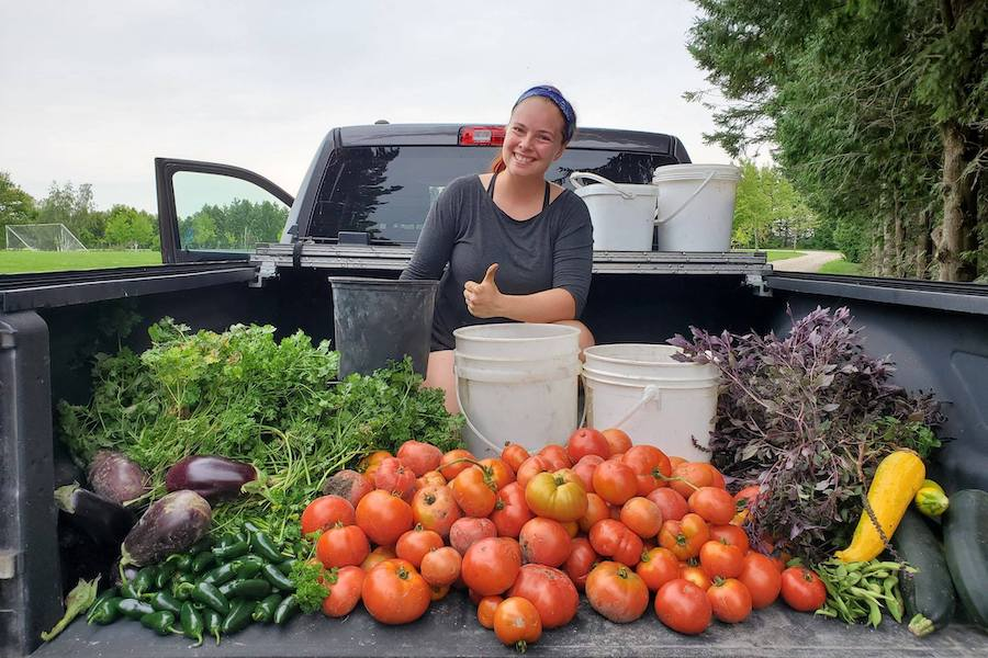A staff member named Hydra sits in the bed of a truck smiling and holding a thumbs up. In front of her on the truck bed is various produce, such as tomatoes, lettuce and squash, that have been collected from the garden at camp.