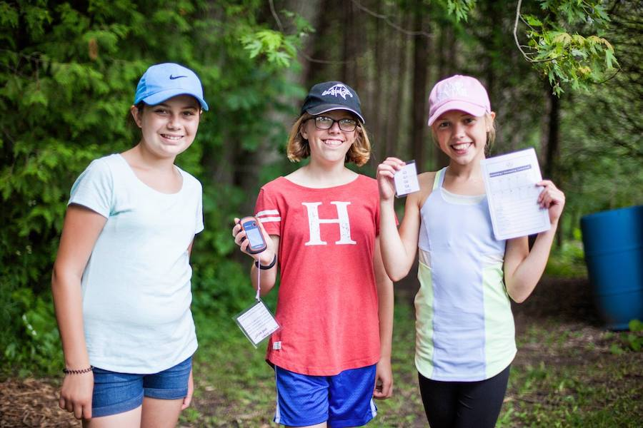 Three campers stand smiling holding their geocaching device and paper where they have recorded what they have discovered at the geocache locations.