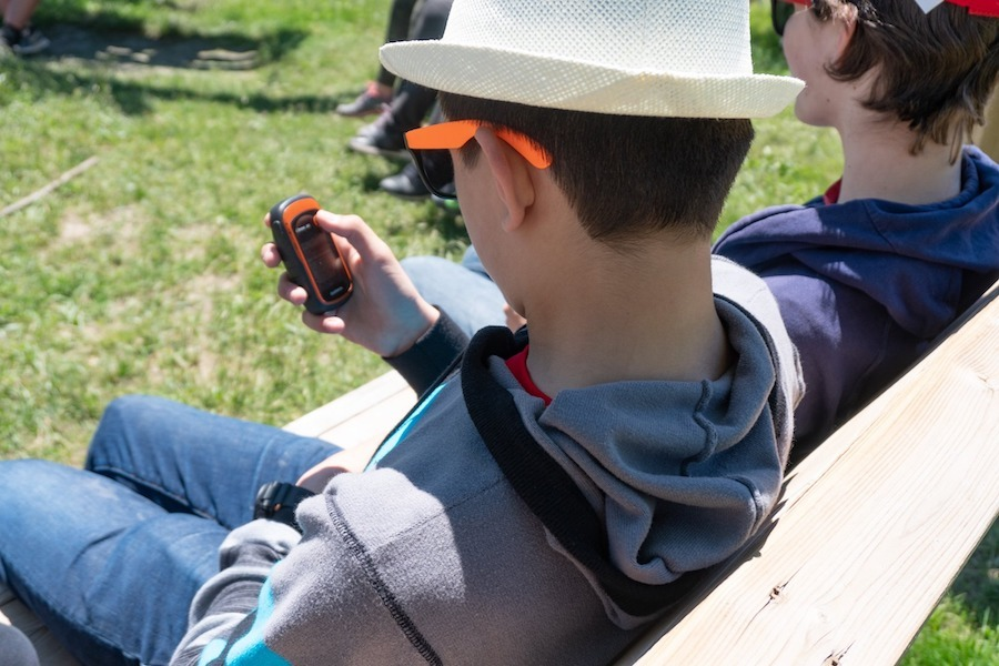 A camper sitting on a wooden bench in at the Swing Circle is looking down at the geocaching device in their hand, learning how to use it.