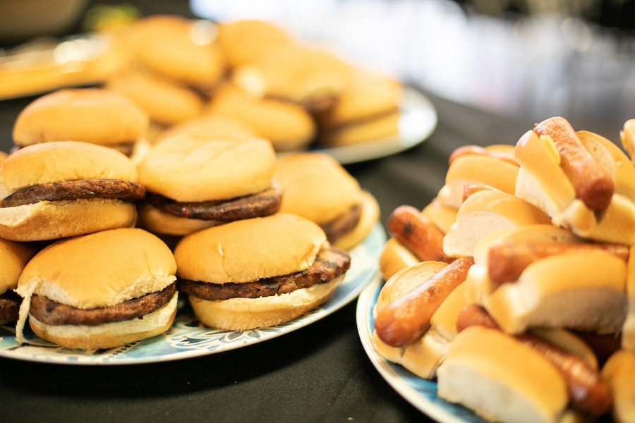 Hamburgers and miniature hot dogs are in buns on trays on the kitchen counter.