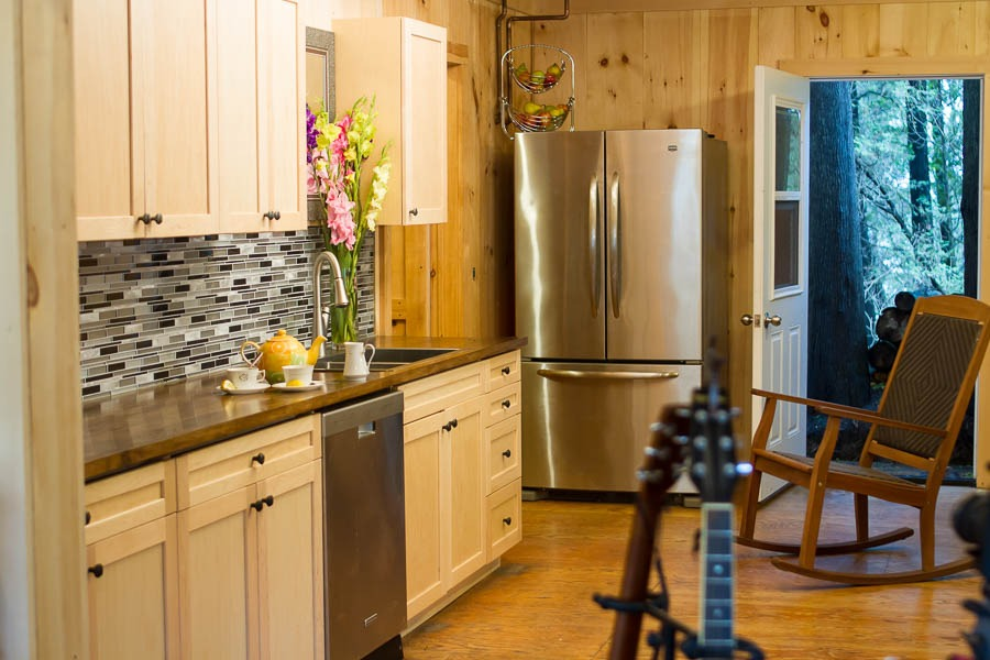 Harmony House kitchen with wooden cabinetry and a stainless steel fridge.