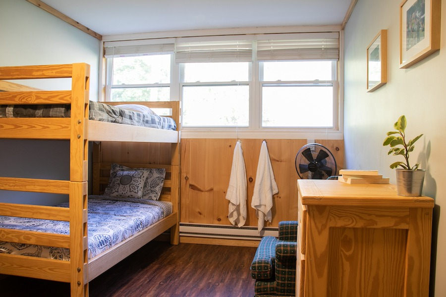 MacDonald Lodge bedroom with single/single bunk bed, chair, and dresser.