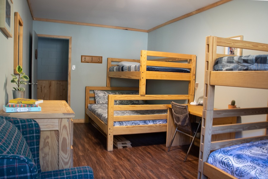 MacDonald Lodge bedroom with queen/single and single/single bunk bed as well as chair and dresser.