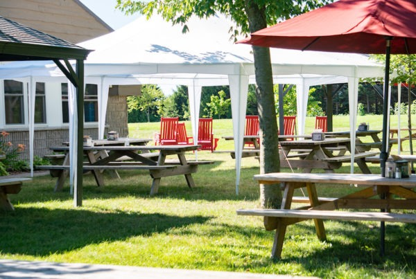 Picnic tables shaded by tents, trees, and umbrellas outside MacDonald Lodge dining hall.