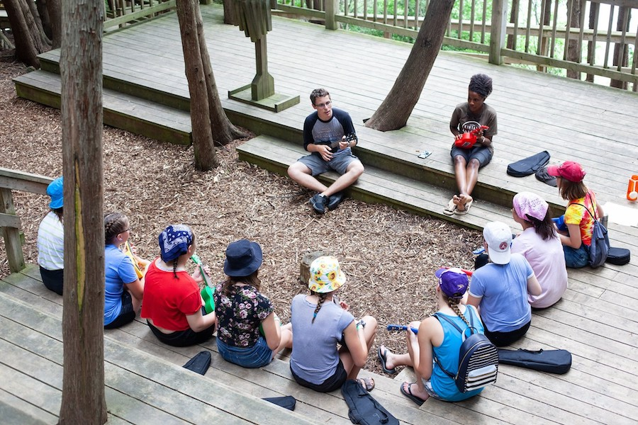 A group of campers sit with ukuleles in their hands watching a staff member named Sound who is teaching them how to play.
