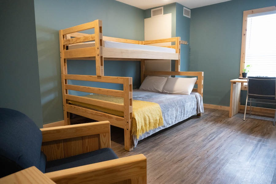 Nest bedroom with single/single bunk bed and a chair.