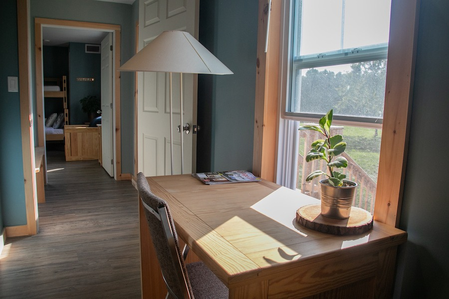 Desk and shared hallways between two Nest bedrooms at overnight summer camp.