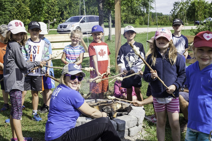 A group of campers and a staff member named Flame are smiling holding sticks with bannock on the ends around a campfire at the Swing Circle.