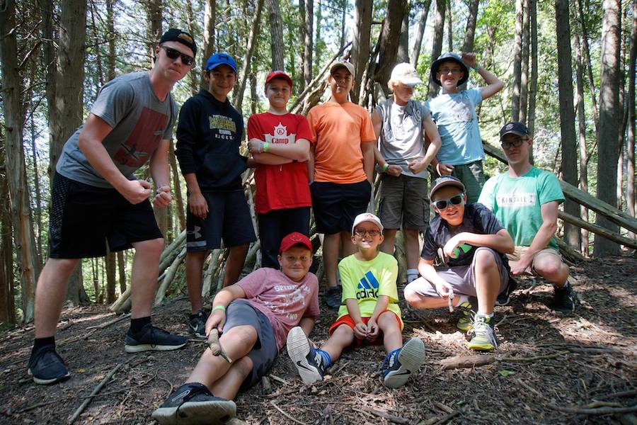 Eight campers and two staff smile posing in front of a stick fort built in the cedar woods.