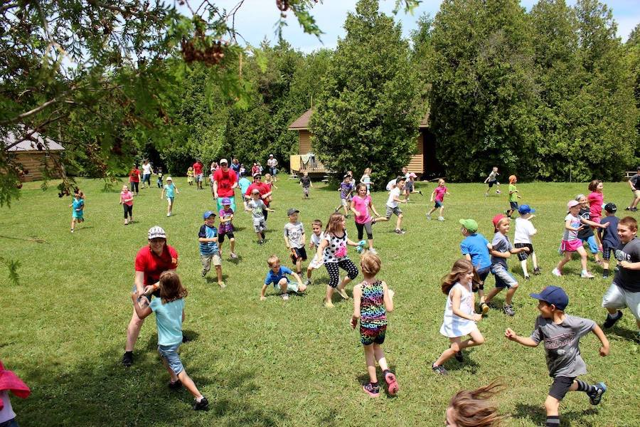 A large group of campers and staff are running in various directions on an open field trying to collect small cups for a game.