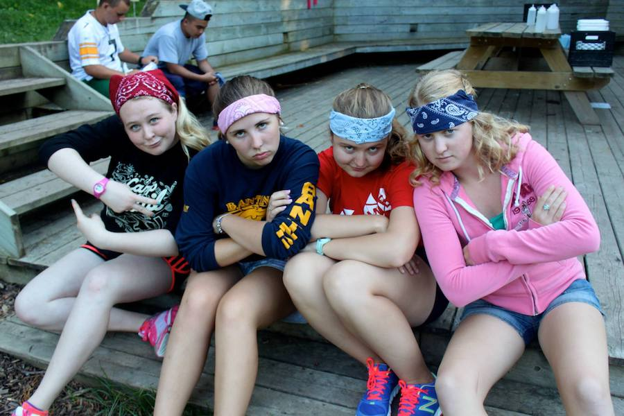 Three campers and one staff member all wearing bandanas across their forehead sit together on a porch with arms crossed making serious faces.