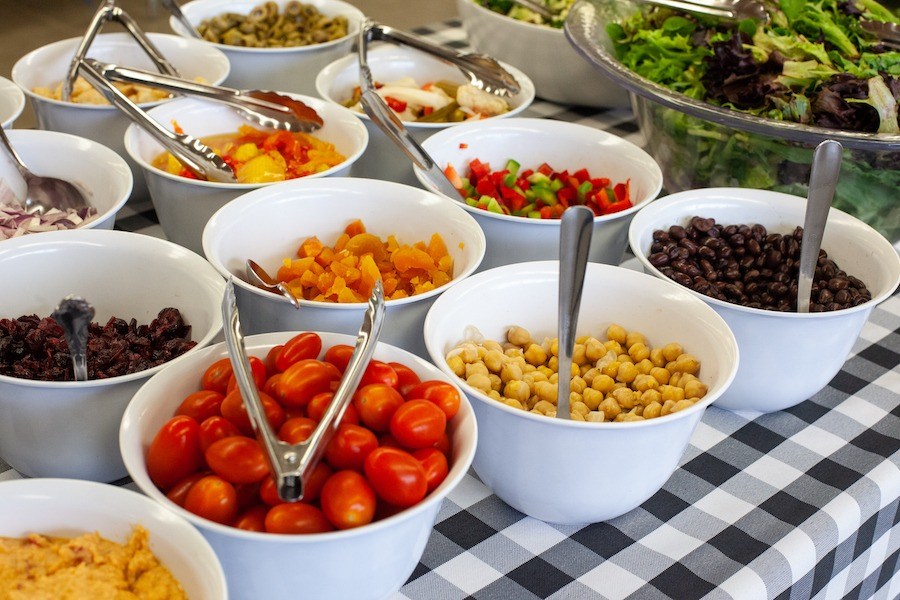Fresh salad and toppings such as cherry tomatoes, chickpeas, peppers, and raisins are in bowls on a buffet for guests to enjoy a delicious salad bar at summer camp.