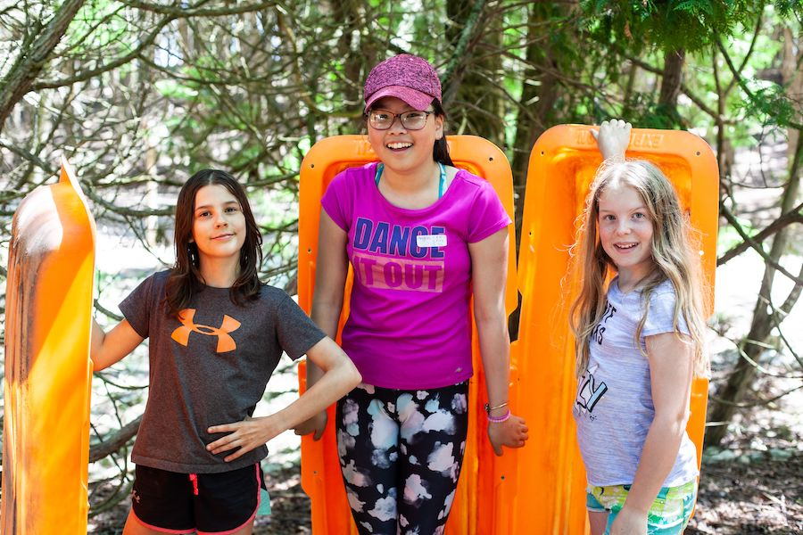 Three campers all holding plastic toboggans pose smiling in from of the 100ft slide at summer camp!