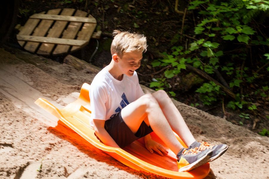 A camper is sitting on a toboggan smiling and laughing after exiting out of the bottom of the 100ft slide into a sandpit.