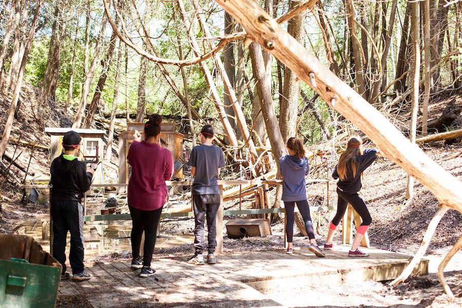 Five participants stand on a wooden platform in the cedar forest with their backs facing us while they aim their slingshots at various items set up in the range.