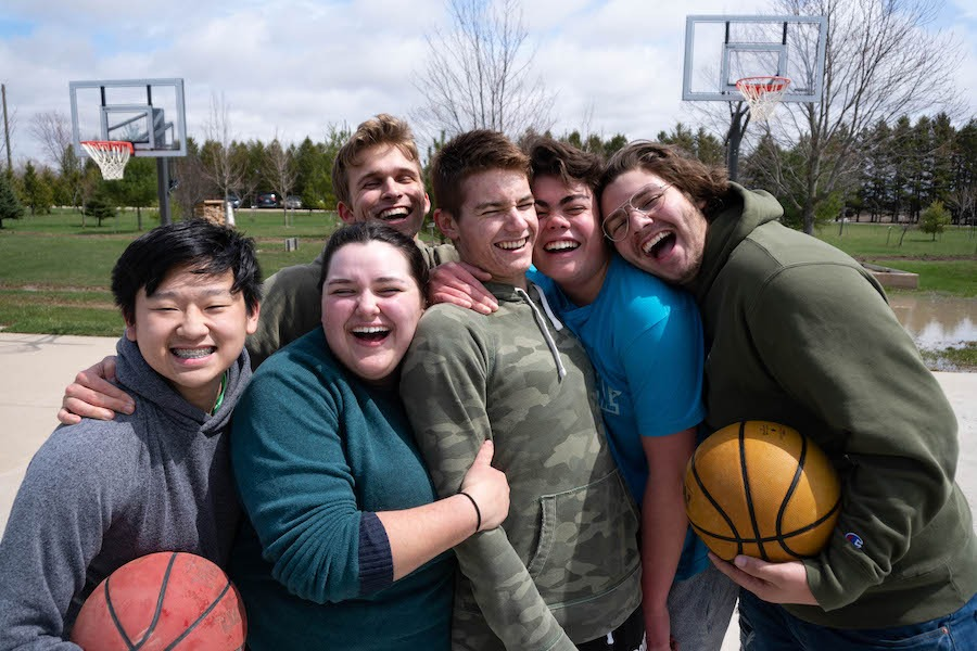 Six staff are smiling and holding one another on an outdoor basketball court. Two staff, one on either side of the group, are holding basketballs.