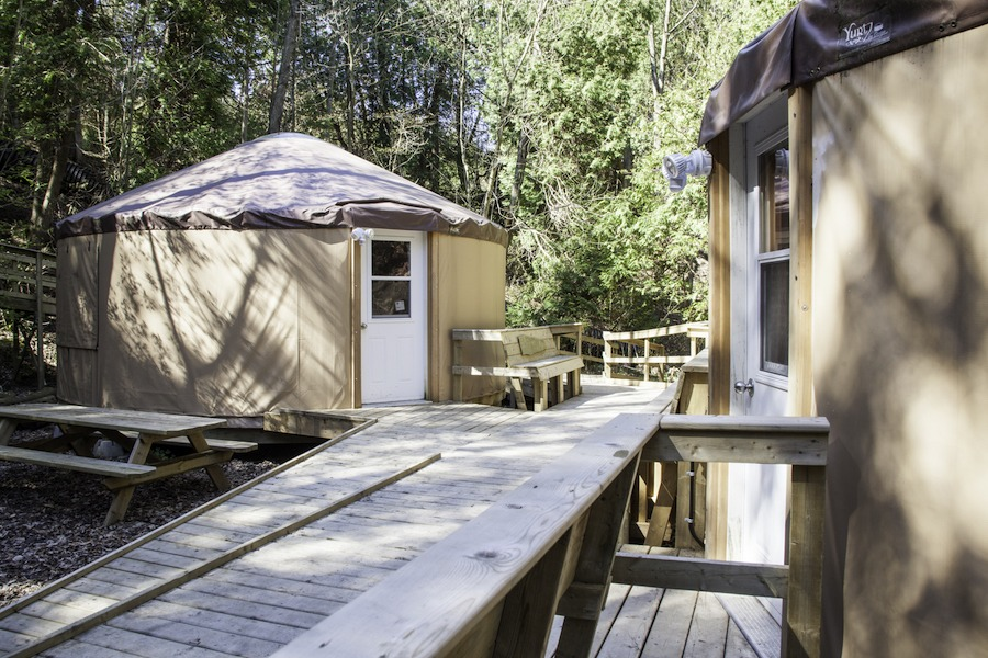 Three Yurts with entrances off a wooden deck in the woods.