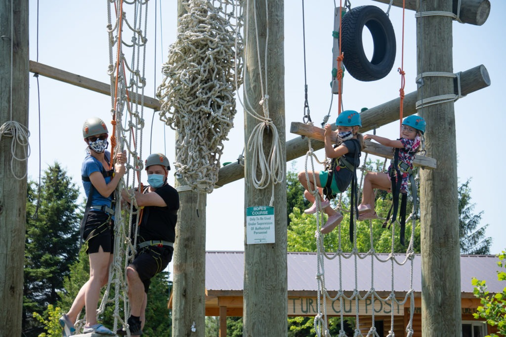 Two adults and two children are climbing the various sides of the Adventure Tower at Camp Kintail's High Challenge Course.