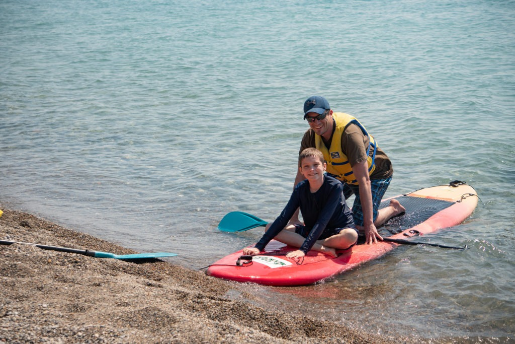 A father and son smile while paddleboarding at Camp Kintail.