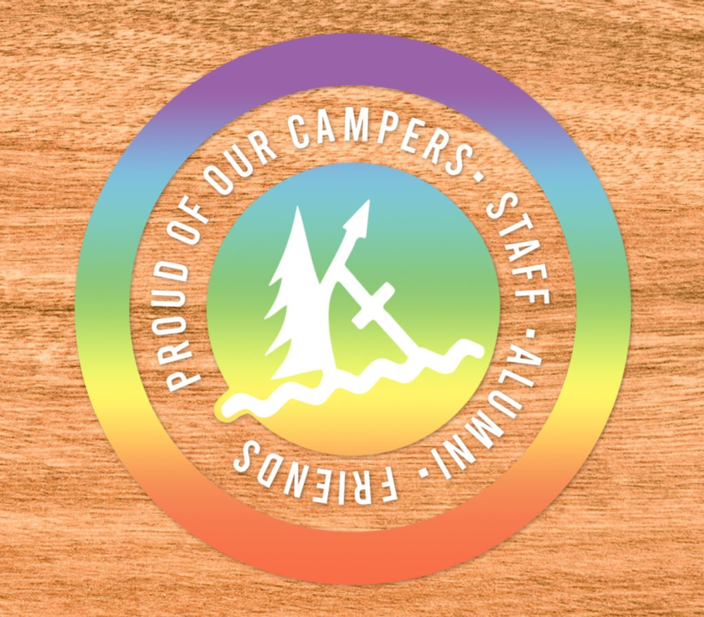 """A circular sticker on a woodgrain background. It has a gradient rainbow overlay, and in white text bordering the kintail logo in the middle is written """"proud of our campers, staff, alumni, friends"""""""