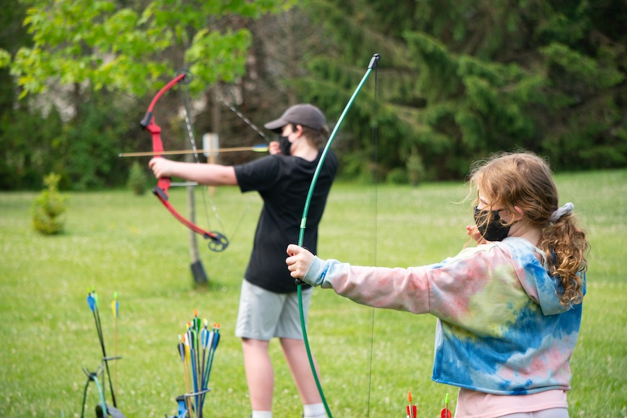 Two campers wearing masks are aiming a loaded bow and arrow at a target to the left.