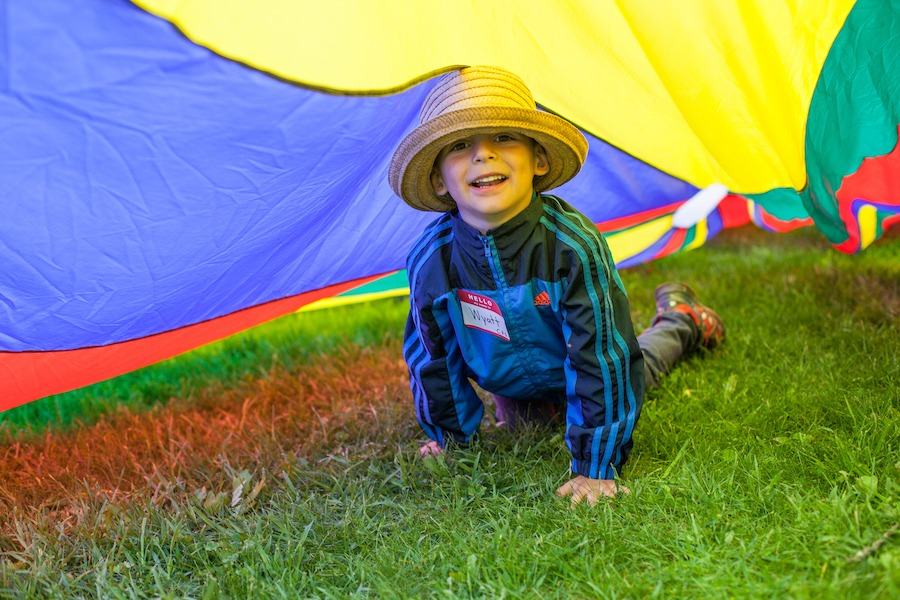 A young camper is on his hands and knees under a colourful parachute smiling.