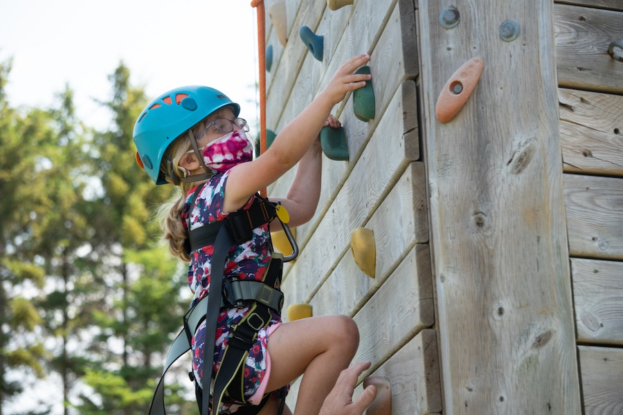 A young camper wearing a mask, helmet, and harness is being belayed while they climb up the rock wall at summer camp.