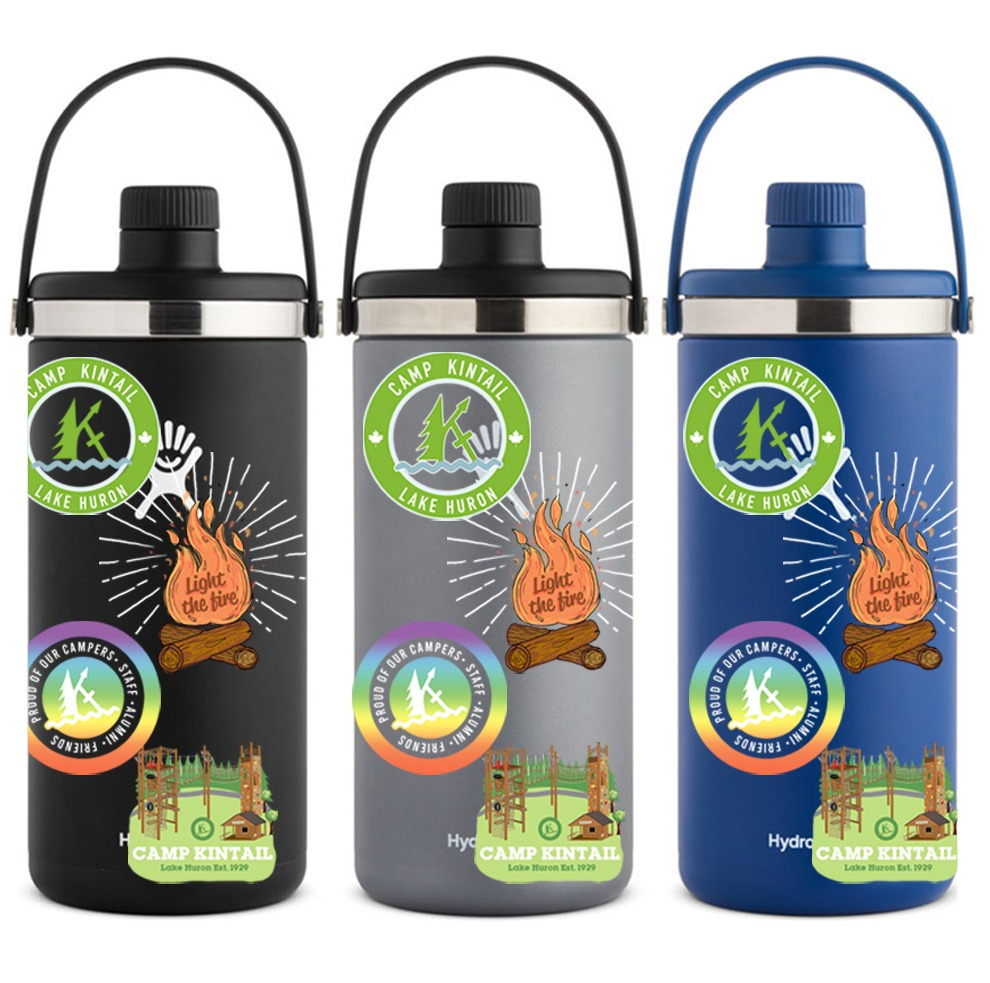 """3 Hydroflask brand waterbottles: black, grey, and dark blue from left to right. Each features a green Kintail logo sticker, an orange sticker in the shape of a campfire reading """"light the fire"""", a Kintail pride sticker, and a sticker with an illustration of the Kintail ropes course."""