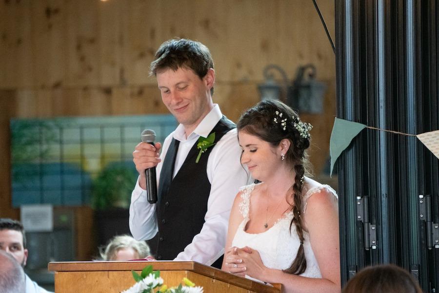 Maddie and Matt stand at the podium making a speech at MacDonald Lodge dining hall.