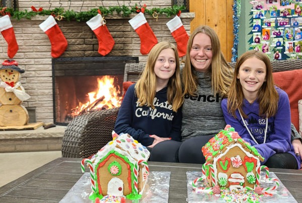 A mother and her daughters pose beside decorated gingerbread houses.