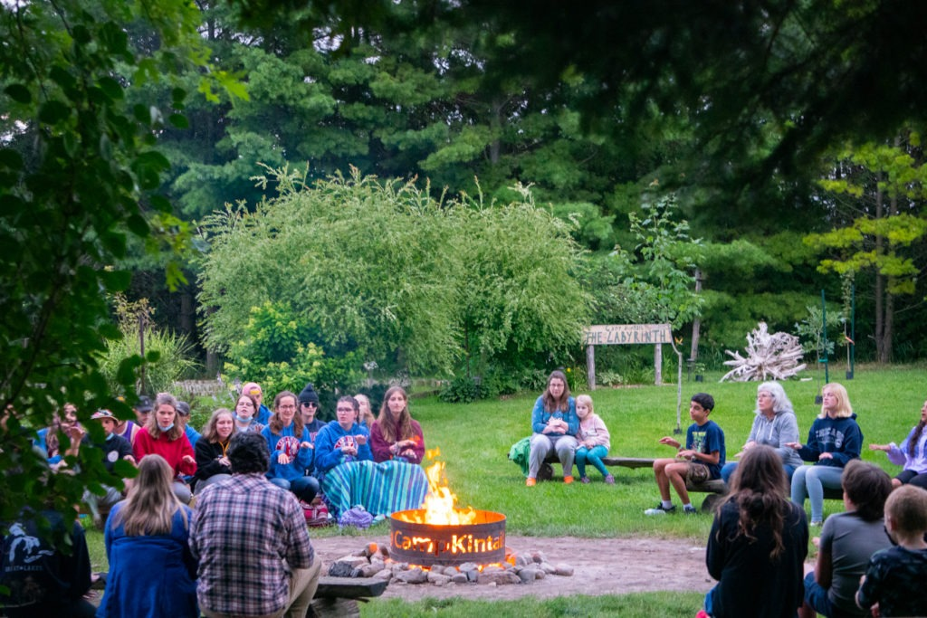 A fire burns surrounded by greenery and small groups of people sitting on benches.