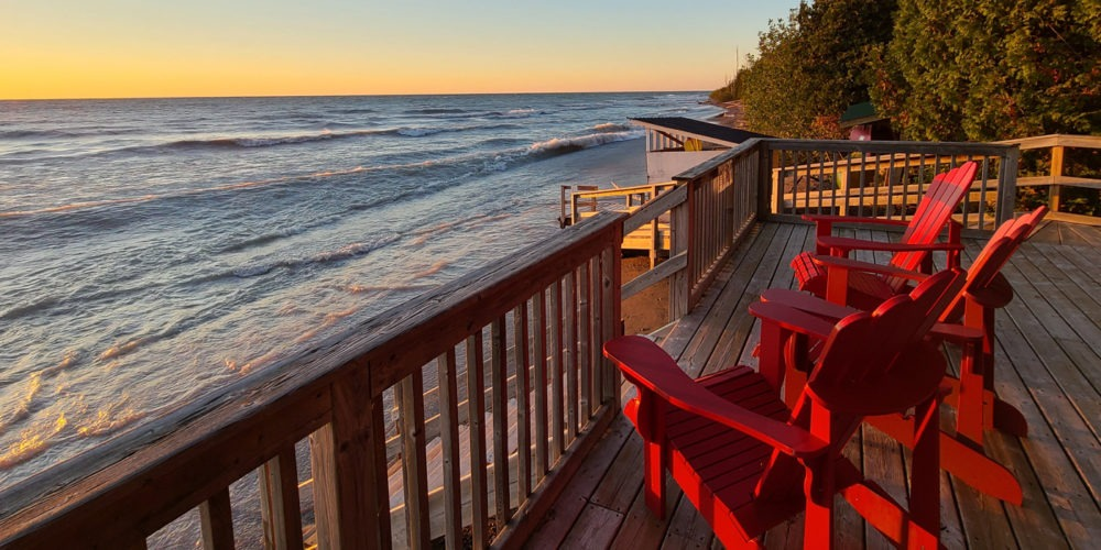 Red chairs face the sunset on a deck overlooking Lake Huron.