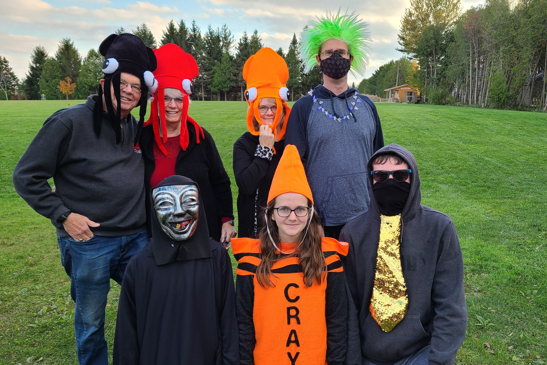 A group of people smile wearing octopus hats and crayon costumes.