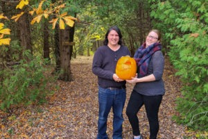 A young man and woman hold a jack-o-lantern standing on a path between trees.