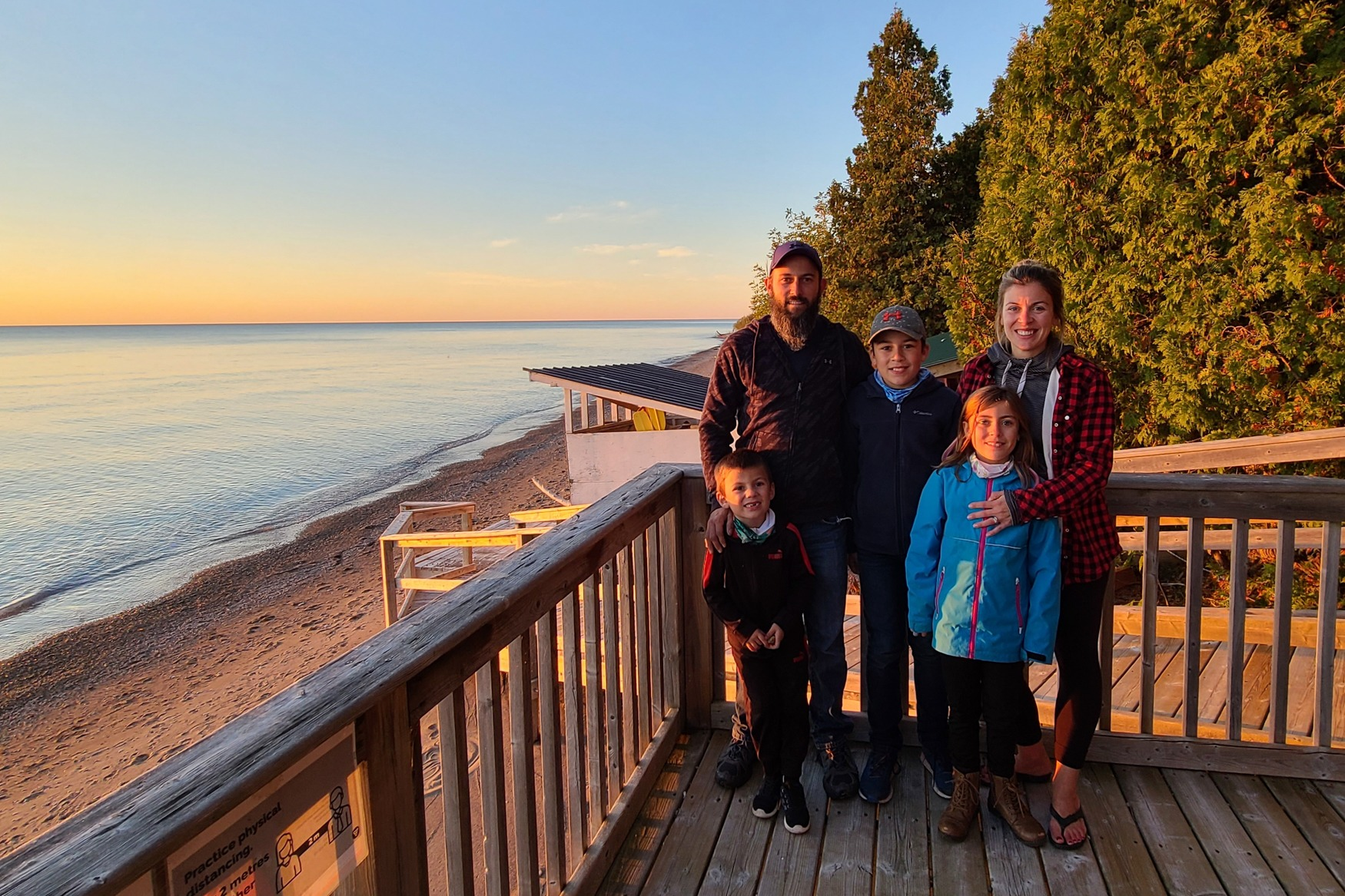 A young family of five stands on the deck at the beach during sunset.