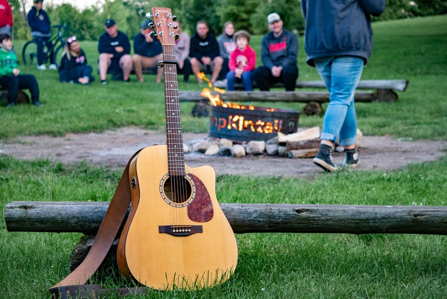 A Guitar sits propped against a bench while people in the distance sing.