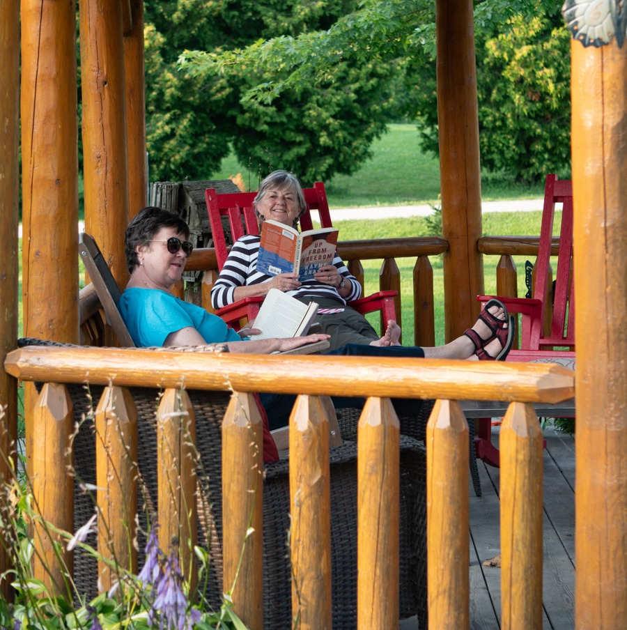 Two women sit reading in red rocking chairs in a gazebo.
