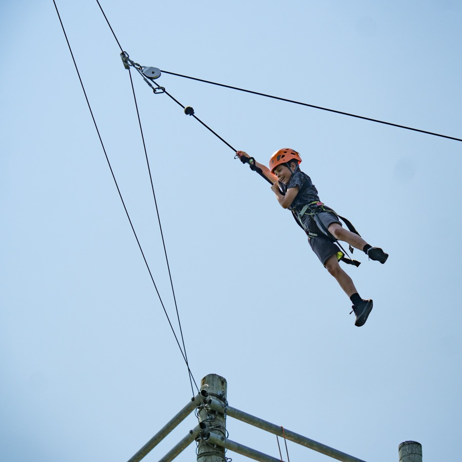 A young boy wearing a harness swings from a secured rope high in the air wearing a helmet.
