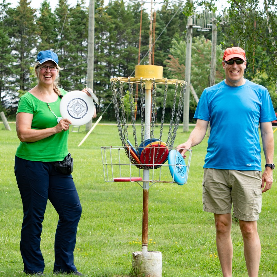 A man and woman her husband pose holding frisbees beside a disc golf catcher.